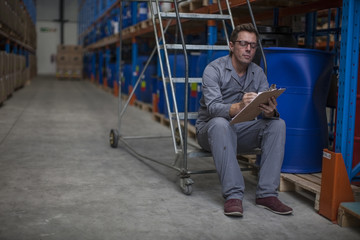 Worker taking stock in warehouse