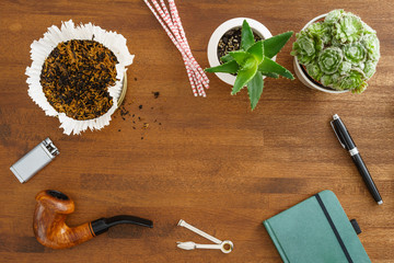 Desktop scene with pipe, succulents, tobacco, notebook and fountain pen shot from above
