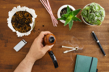 Mansmoking his pipe desktop scene with pipe and succulents shot from above