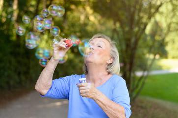 Happy senior woman having fun blowing bubbles