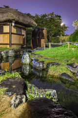 korean traditional house with water mill and stream in rainy night