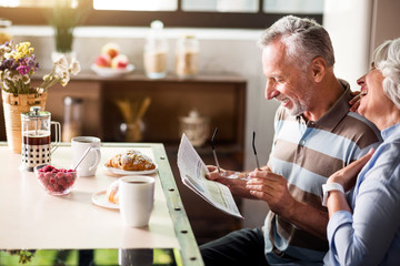 Elderly caucasian male and female reading the newspaper