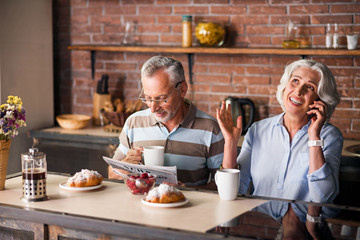 Joyful senior citizen couple drinking coffee together in the kitchen