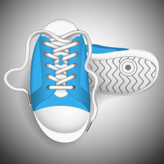 Blue sneakers on a grey background.