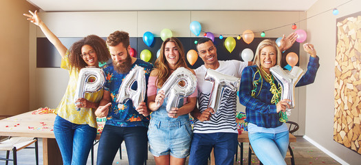 Group holding balloons spelling the word PARTY