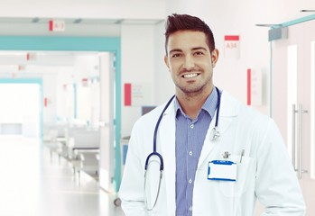 Happy young physician standing at hospital hallway