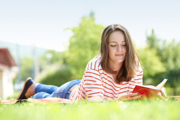 Full length shot of a beautiful young woman reading book while relaxing at park.