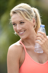 Fitness girl drinking water after exercising