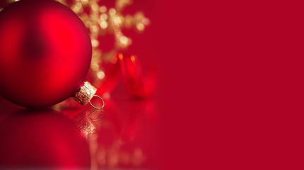 Golden and red christmas ornaments on red background with copy space. Merry christmas card. Winter holidays. Xmas theme.
