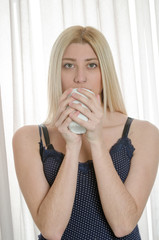 Woman with green eyes and pretty face holding a cup of hot coffee, home curtain as background