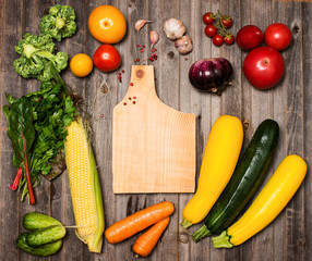 Vegetables and ingredients for cooking around cutting board
