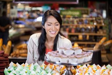 Happy woman looking at cupcakes