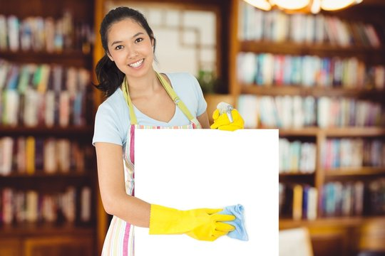 Composite image of cheerful woman wiping down white surface