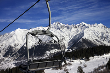 Chair-lift at ski resort and snow winter mountains in nice sun d