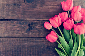 Bouquet of red tulips on a wooden background. Spring flowers.