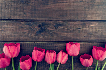 Row of tulips on wooden background with space for message.