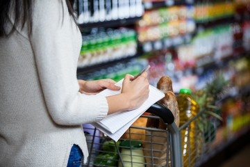 Woman writing on notepad while shopping in grocery section