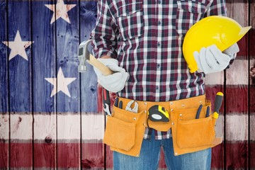 Composite image of handyman holding hard hat and hammer
