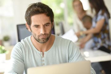 Man in office working on laptop