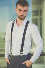 Man with beard is wearing suspenders