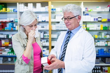 Pharmacist showing medicine to customer
