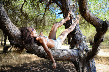 Sexy bikini model relaxing on a tree, nature outdoors background