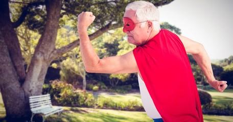 Composite image of senior man pretending to be a superhero