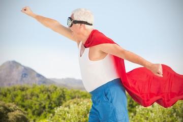 Composite image of senior man wearing superman costume