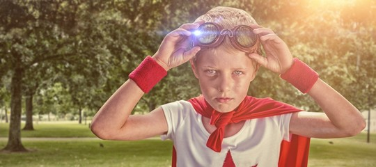 Composite image of little boy pretending to be superhero