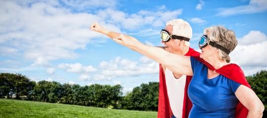 Composite image of senior couple wearing superman costume