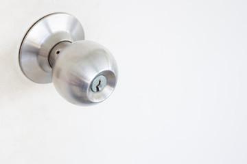 Doorknob in wooden door close up.