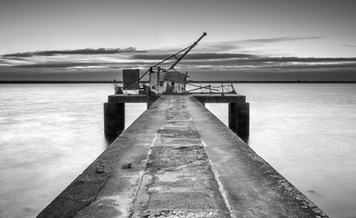 Ancient industrial pier, black and white pier with hoist