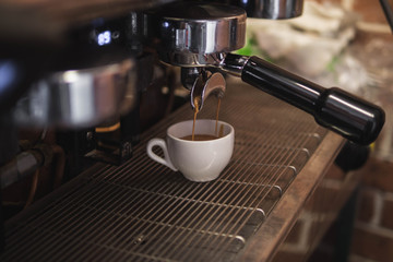 Close-Up Of Coffee Pouring In Cup From Machine