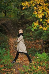 blonde girl walks on autumn park and touches hands with yellow leaves trees