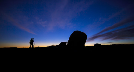 Silhouette of a photographer working and hiking in a desert landscape at night