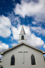white church with cross outside verticle view with blue sky with white puffy clouds