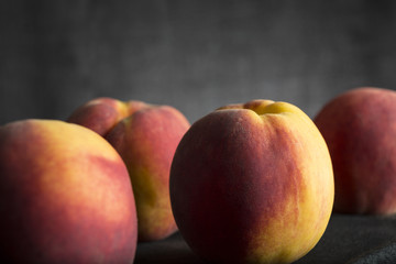 Healthy fresh peaches on dark background
