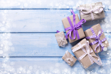 Different  festive gift boxes with presents on blue wooden backg