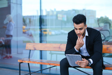 Man in suit arabic puts on sunglasses with tablet near business