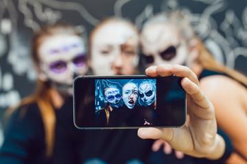 Three girls going on Halloween, grimace make selfie  a dark background with  pattern