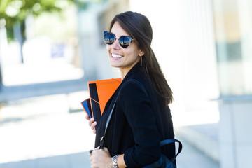Beautiful young woman walking in the street.