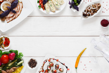 Variety of snacks for traditional tableful, free space. Delicious homemade meals with glass decanter with vodka on white wooden background, flat lay, copy space, frame