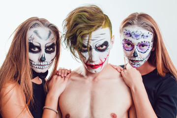 Two girls and a guy with Halloween face art on white background