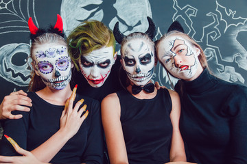 Three girls and a guy with Halloween face art on dark background pattern
