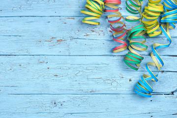bunte Luftschlangen auf blauen Holzbrett - Karnevalsdeko
