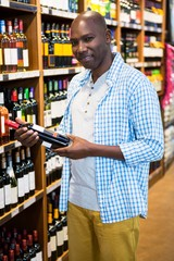Man looking at wine bottle in grocery section at supermarket