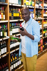 Man looking at wine bottle in grocery section