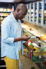 Man using mobile phone in grocery section while shopping