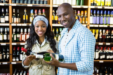 Couple looking at wine bottle in grocery section at supermarket