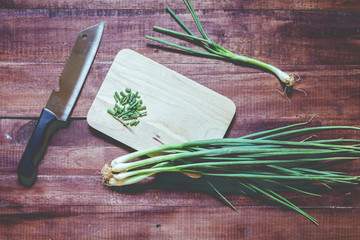 Green onions with Knife on chopping board on wooden background